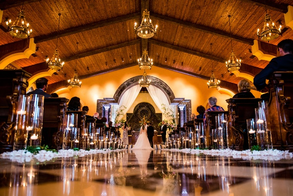 Flower petals and candles along aisle checker floor at San Diego venue wood beam ceiling