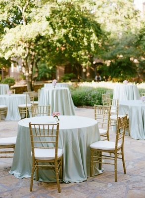 cocktail table with pale green tablecloth and gold chiavari chairs