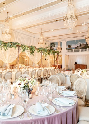 wedding reception ballroom chandelier round table lavender linen oval back wood cane chairs greenery