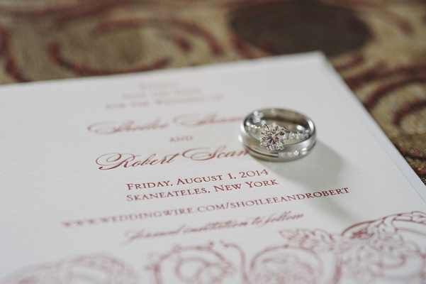 Engagement ring and wedding bands on invitation