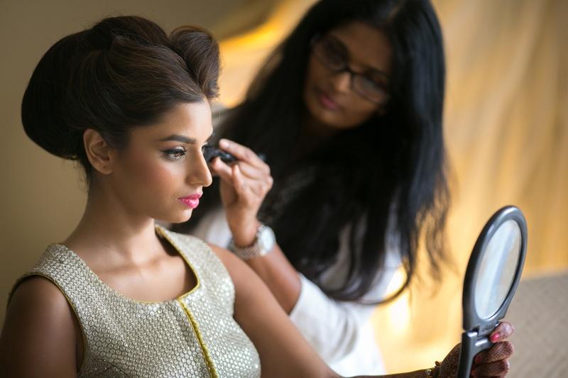 indian-american bride looks in mirror as makeup artist applies mascara