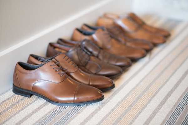 Pairs of groomsmen tan leather shoes lined up against the wall