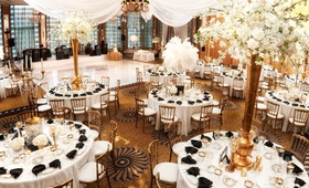 White tables gold chairs centerpieces black napkins drapery dance floor Chicago