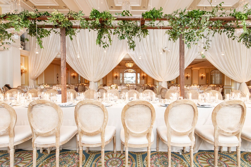 wedding reception long table wood cane chairs and arbor overhead drapery greenery french garden