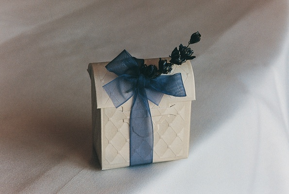 Ivory favor boxes tied with sheer ribbon and sprig