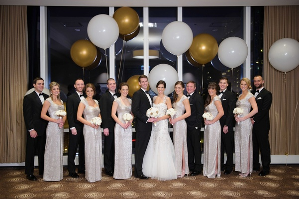 new year's eve bridal party in front of window and large gold and white balloons