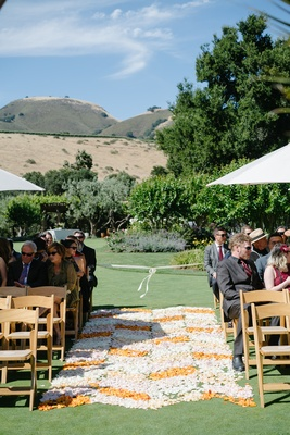 orange, blush, and white flower petals form chevron-patterned aisle