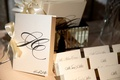 White ceremony program with ivory satin bow and calligraphy on escort cards