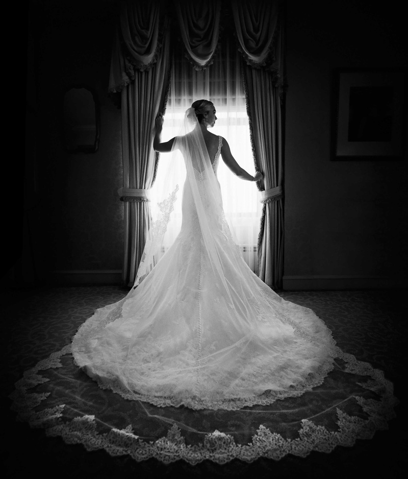 black and white photo of bride in matthew christopher and nymphi cathedral veil, lace