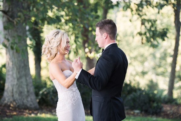Bride in strapless wedding dress holds groom's hands in forest strapless gown loose updo hairstyle