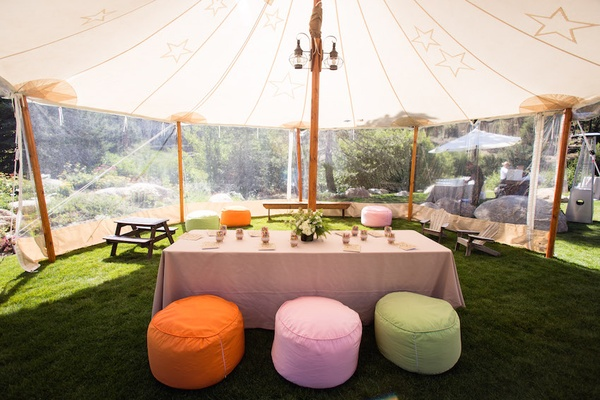 Outdoor tent with clear windows and colorful ottomans