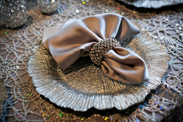Silver satin table linens with pearl overlay and silver charger plate with matching napkin ring