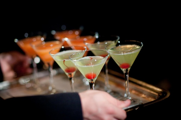 Light green martini with red cherry and orange martinis