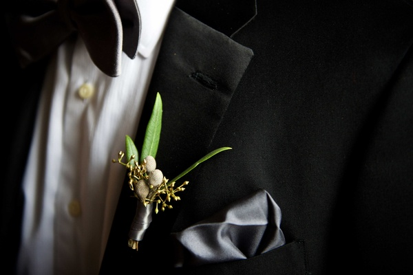 Groom in tuxedo with grey silk pocket square and fall boutonniere with green leaves