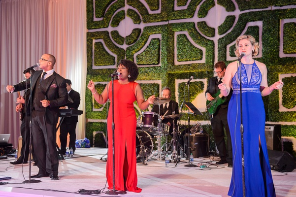 Wedding reception entertainment live band singers in red blue evening gowns hedge wall