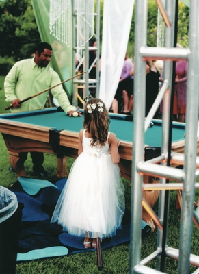 Flower girl watching guest play pool at custom blue suede pool tables