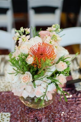 Wedding shower centerpiece of pink and white hydrangeas, roses, greenery, and orange protea flower