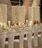 chandelier of flower petals on strings, ruched white chair covers