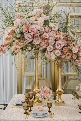tall floral arrangements with roses in varying shades of pink and greenery in gold vase taupe linen