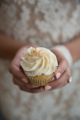 Bride holds cupckae with white frosting and gilded sugar