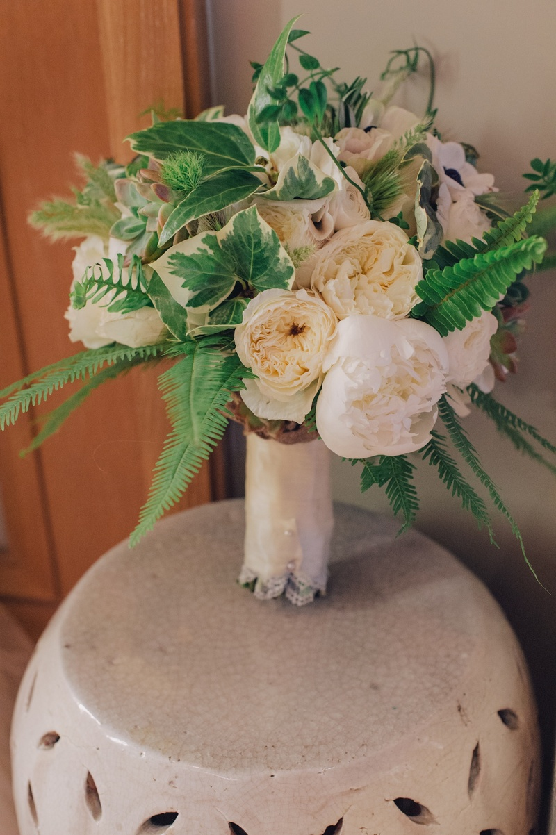White and green flowers tied with lace on ceramic drum