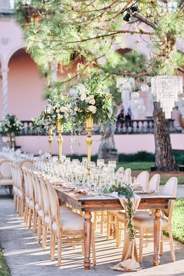 ringling museum wedding reception with long wooden table, gold centerpiece stands
