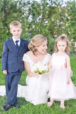Bride in a lace Watters dress with cap sleeves, ring bearer in blue suit, flower girl in pink dress
