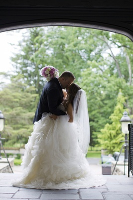 Bride in strapless Lazaro dress with full ruffled skirt, veil, kisses groom in black tuxedo