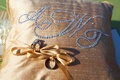 Gold ribbons tie rings to monogram pillow