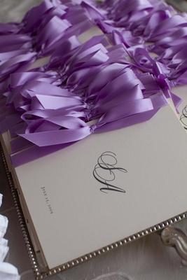 Ceremony program with monogram tied with purple bow