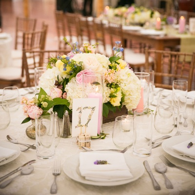 watercolor table numbers with low floral centerpieces and colorful candles in hurricances