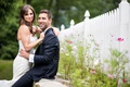 wedding portrait bride in strapless wedding dress with groom in suit white picket fence and greenery