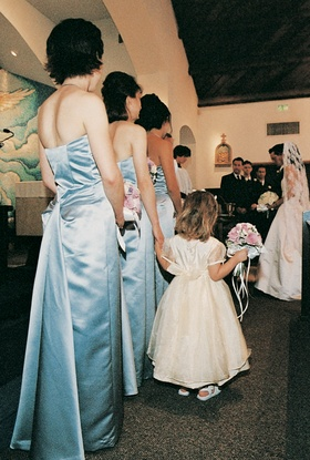 Bridesmaids at ceremony wearing long light blue gowns