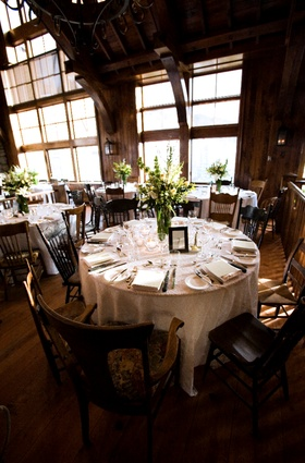 wooden lodge with tall windows and tables covered in white linens