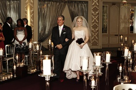 Bride in a pale pink Amsale gown and veil walks down the aisle with father in a black tuxedo and tie