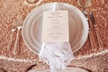 White plate with lace trim napkin and menu on sequin tablecloth