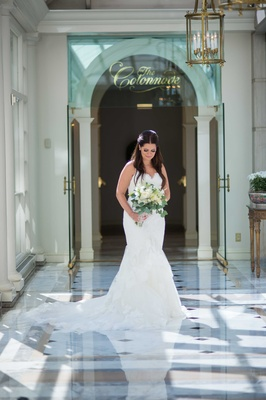 a bride in a stunning white trumpet gown with a train glances at her bouquet white flowers foliage