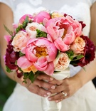 Bride holding bouquet of hot pink peony garden rose and red burgundy blooms