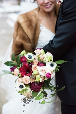 Bride in fur stole and white wedding dress colorful bouquet anemone greenery rose pink red blue