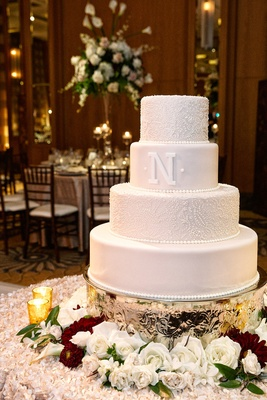 a four-tier white wedding cake with intricate detailing and letter n surrounded wine white flowers
