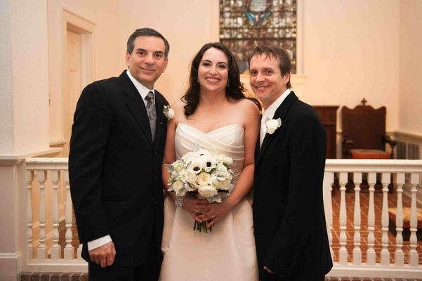 Bride with two men in black suits with white boutonnieres