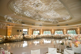 Classic wedding reception decorations with scroll pattern projection gobo on ceiling over dance floo