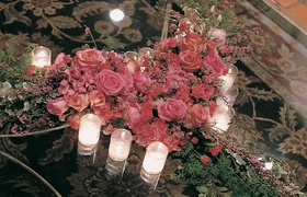 Votive candles and pink rose heart on table