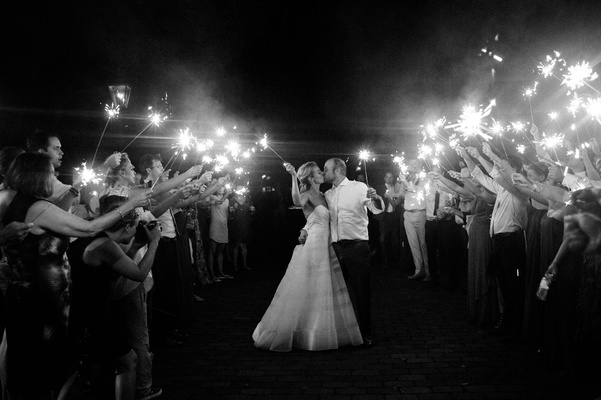 black and white photo of bride and groom kissing during sparkler exit holding sparklers guest tunnel