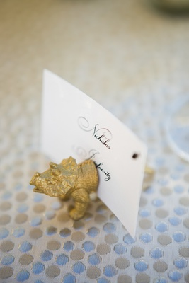 small gold figurine of triceratops dinosaur to hold place card