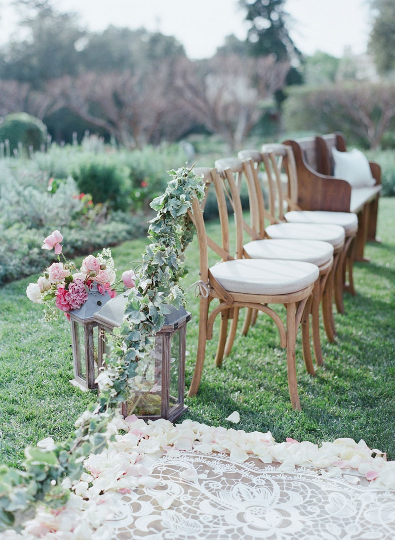 White lace laser cut aisle runner with flower petal garland wood chairs with white cushions, lantern