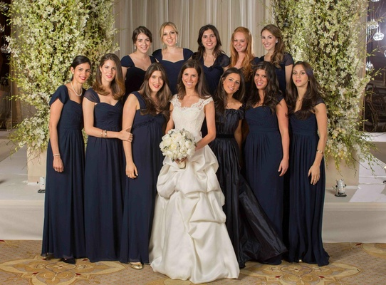 Bride in a Monique Lhuillier gown with bridesmaid's in long navy blue Monique Lhuillier dresses