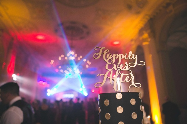 Black and gold polka dot wedding cake with Happily Ever After modern calligraphy cake topper lights