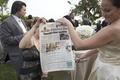 Wedding guests holding custom newspaper
