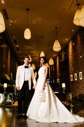 bride in inbal dror ball gown, orchid bouquet, groom in white tuxedo jacket, warmly lit hallway